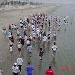 The crowd of racers heading down the beach from the start line.