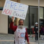 Ken Bob runs with the Free Acai Bowls sign