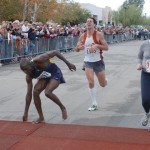 Bassirima Soro swoops his timing chip across the matt at the finish of Tucson Marathon in 2004 photo courtesy of David Bluestein