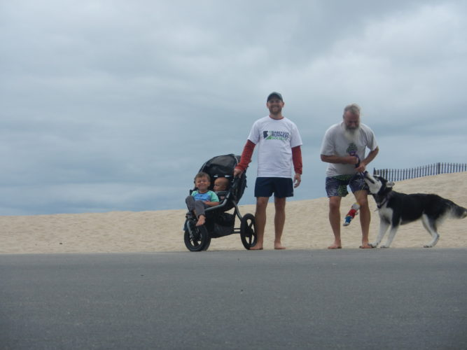 two boys in stroller, Alan, Ken Bob, Mr. Bill (hanging from Kay's leash, and Kay playing Tug 'O' war with leash